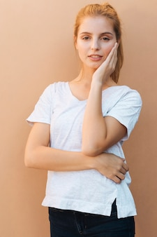 Porträt einer blonden jungen frau mit ihren händen auf dem kinn, das kamera betrachtet