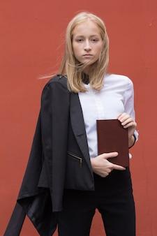 Porträt einer blonden jungen lächelnden frau lokalisiert auf hintergrund mit notizbuch. studentenleben. lehrertag