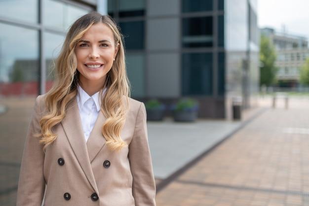 Porträt einer blonden lächelnden geschäftsfrau vor ihrem büro