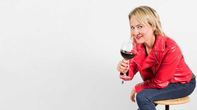 Porträt einer blonden reifen frau, die in der hand rotweinglas lokalisiert auf weißem hintergrund hält