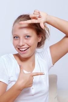 Porträt einer blonden teenager-mädchenfrau, die rahmen mit den fingern macht.