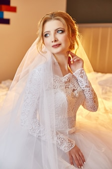 Porträt einer braut, die in einem schicken weißen hochzeitskleid auf dem bett sitzt und sich auf die hochzeitszeremonie vorbereitet. blonde frau in einem weißen kleid und einem schleier auf dem kopf. die braut wartet auf ihren bräutigam