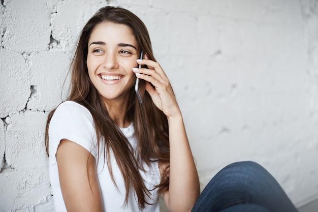 Porträt einer breit lächelnden erwachsenen europäischen frau in der freizeitkleidung, die beiseite schaut, während sie sich an die wand lehnt und über das mobiltelefon spricht. mädchen nutzt wlan, um mit einem freund zu sprechen, der im ausland studiert.