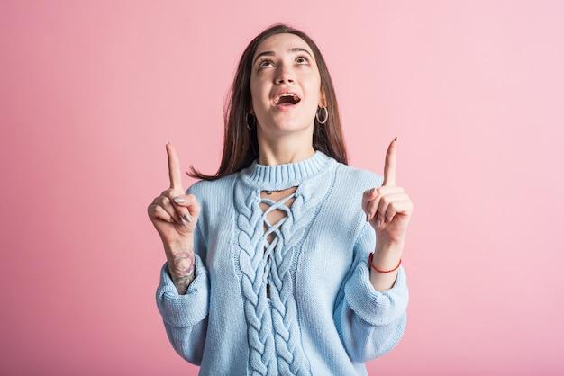 Porträt einer brünette auf einem rosa hintergrund, die ihre finger nach oben zeigt