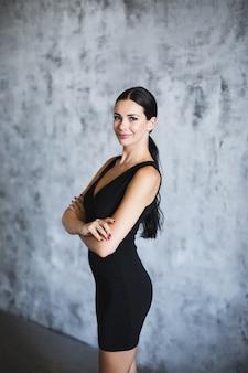 Porträt einer brünette in einem schwarzen kleid auf einem kunsthintergrund.
