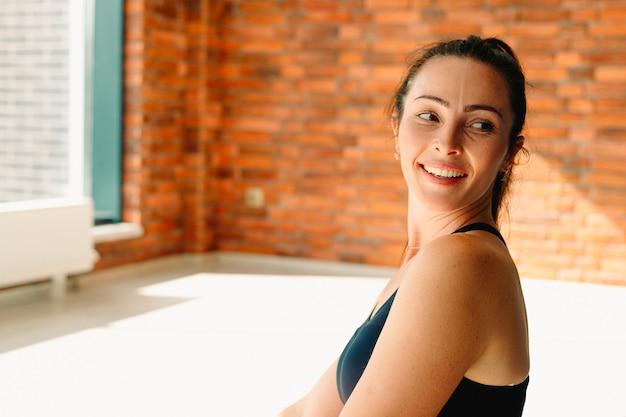 Porträt einer brünetten. eine gesunde, starke frau mit einem glücklichen lächeln. im fitnessstudio während des trainings. foto mit leerem seitenraum.