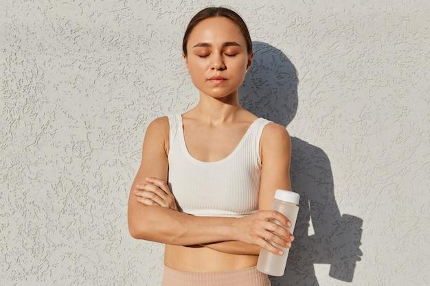 Porträt einer brünetten frau, die ein weißes sportliches oberteil trägt, das mit geschlossenem ja steht, eine flasche mit wasser hält und nach dem training in der nähe der lichtwand im freien fotografiert wird.