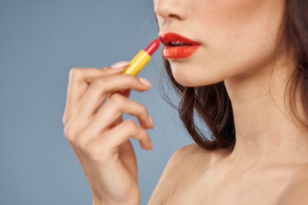 Porträt einer brünetten mit rotem lippenstift auf den lippen, eine schöne frau malt ihre lippen mit lippenstift