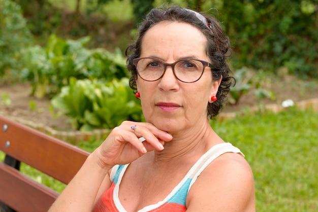 Porträt einer brunettefrau von mittlerem alter mit den brillen, im freien