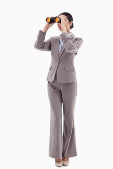 Porträt einer brunettegeschäftsfrau, die durch ferngläser gegen einen weißen hintergrund schaut