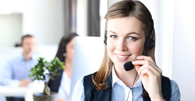 Porträt einer callcenter-mitarbeiterin in begleitung ihres teams. lächelnder kundendienstmitarbeiter bei der arbeit.