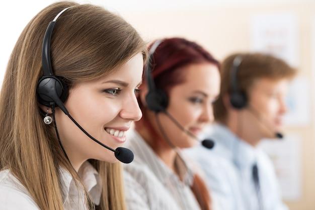 Porträt einer callcenter-mitarbeiterin in begleitung ihres teams