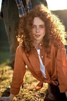 Porträt einer charmanten dame in freizeithemd, die sich bei sonnenuntergang in der natur ausruht, blick auf die kamera posiert...
