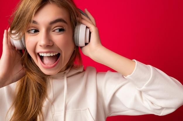 Porträt einer charmanten emotionalen positiven jungen blonden frau, die einen weißen hoodie trägt, isoliert über