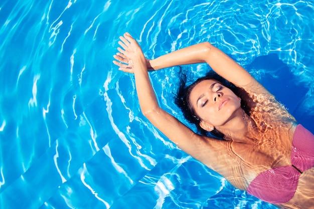 Porträt einer charmanten frau, die im pool schwimmt