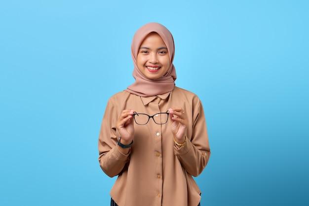 Porträt einer charmanten jungen asiatin mit brille auf blauem hintergrund