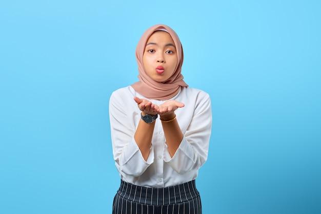 Porträt einer charmanten jungen asiatischen frau, die handflächen hält, senden dem freund einen luftkuss