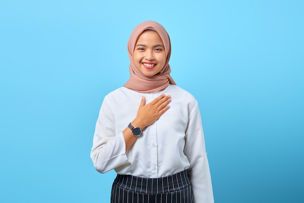 Porträt einer charmanten jungen asiatischen frau, die stolz auf blauem hintergrund die hände auf die brust legt
