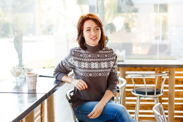 Porträt einer charmanten jungen frau mit freundlichem lächeln, brünett in einem strickpullover, der wi . anlächelt
