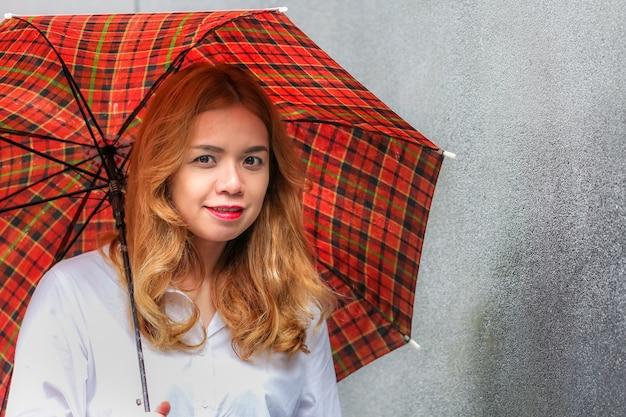 Porträt einer dame, die einen roten regenschirm hält