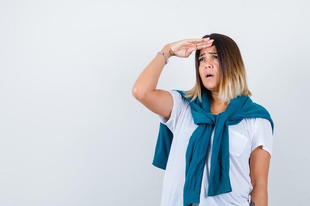 Porträt einer dame mit gebundenem pullover, die weit weg mit der hand über dem kopf in weißem t-shirt schaut und fokussierte vorderansicht schaut
