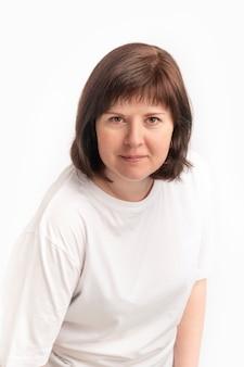 Porträt einer dunkelhaarigen frau mittleren alters in einem weißen t-shirt auf weißem hintergrund. damenhaarschnitt mit pony.