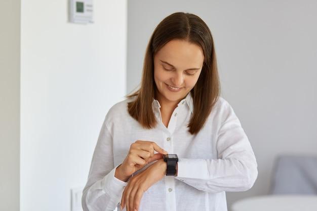 Porträt einer dunkelhaarigen, glücklichen, optimistischen frau mit weißem hemd, die ihre armbanduhr mit glücklichem gesichtsausdruck betrachtet, sie berührt, moderne technologie.
