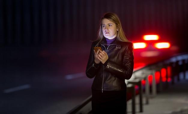 Porträt einer einsamen frau, die an der dunklen autobahn aufwirft