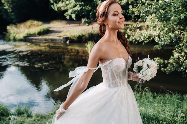 Porträt einer eleganten braut in einem weißen kleid mit einem blumenstrauß in der natur in einem naturpark.modell in einem hochzeitskleid und handschuhen und mit einem blumenstrauß .belarus