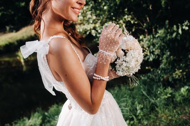Porträt einer eleganten braut in einem weißen kleid mit einem blumenstrauß in der natur in einem naturpark. modell in einem hochzeitskleid und handschuhen und mit einem blumenstrauß. belarus.