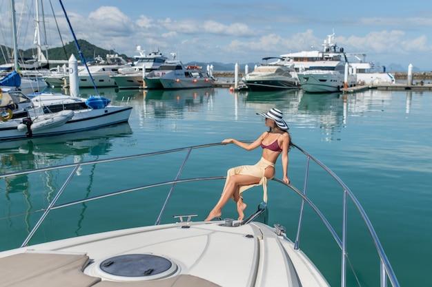 Porträt einer eleganten dame am hafen. ein kleiner hafen mit yachten und segelbooten