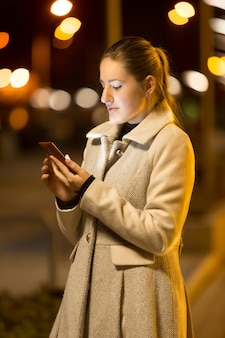 Porträt einer eleganten frau, die nachts eine textnachricht auf der straße schreibt