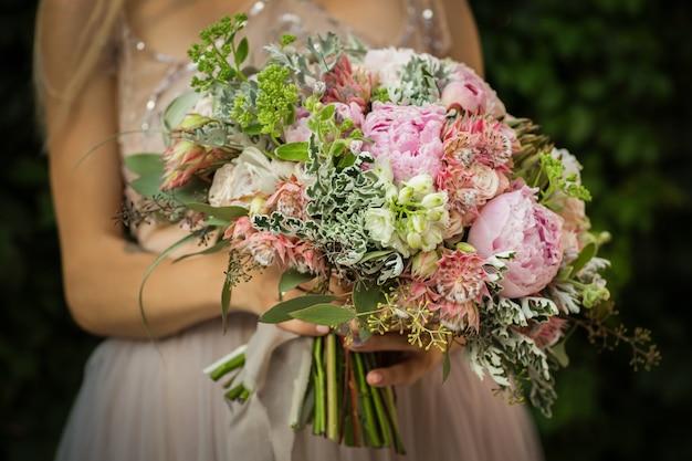 Porträt einer eleganten unerkennbaren hübschen frau, die graues hochzeitskleid trägt und in der straße aufwirft. die braut hält einen strauß pastellblumen und viel grün