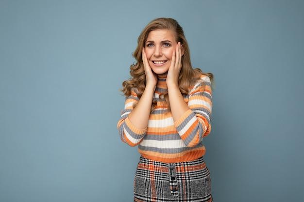 Porträt einer emotionalen jungen, schönen blonden, lockigen frau mit aufrichtigen emotionen, die einen stylischen gestreiften pullover trägt, der auf blauem hintergrund mit leerem raum isoliert ist und nervös und besorgt aussieht