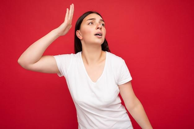 Porträt einer emotionalen jungen, schönen brünetten frau mit aufrichtigen emotionen, die ein weißes t-shirt für das modell trägt, einzeln auf rotem hintergrund mit freiem platz.