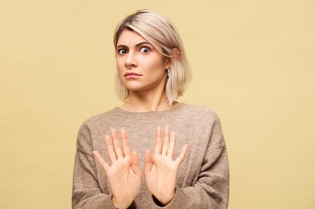 Porträt einer empörten wütenden jungen europäischen blonden frau, die empörung ausdrückt, die hände ausstreckt, eine nein- oder stopp-geste macht und sagt: bleib weg von mir, während du mit ihrem freund kämpfst