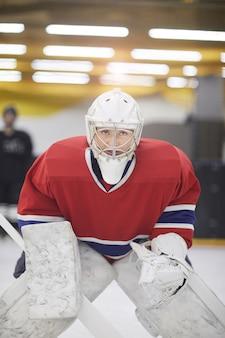Porträt einer entschlossenen hockeyspielerin in voller ausrüstung