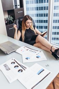 Porträt einer entspannten chefin, die am arbeitsplatz mit füßen auf dem tisch sitzt und ihren arbeitstag plant, ziele im notizbuch zu schreiben.