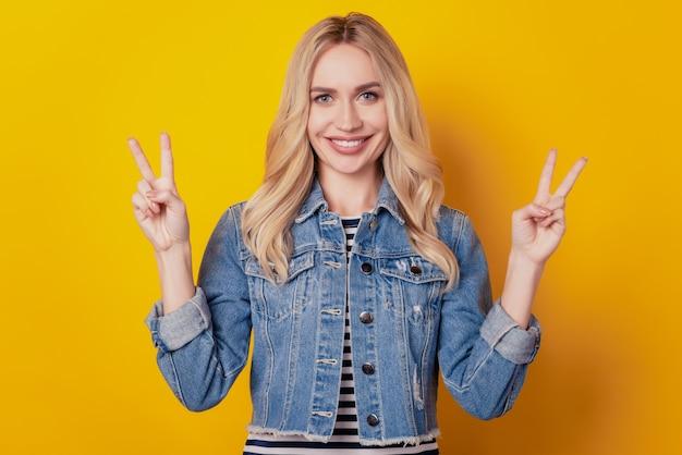 Porträt einer entzückenden charmanten dame zeigt zwei v-zeichen zahniges lächeln auf gelbem hintergrund