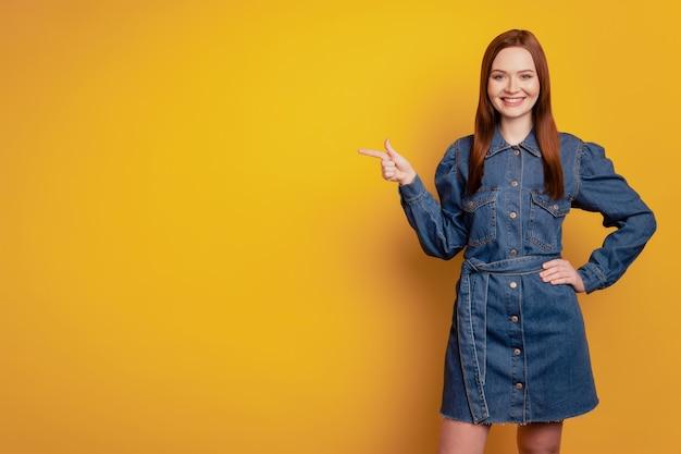 Porträt einer entzückenden dame zeigt an, dass der zeigefinger leeren raum trägt, ein kurzes kleid auf gelbem hintergrund trägt