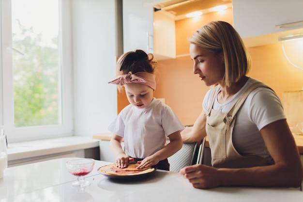 Porträt einer entzückenden mutter und einer tochter, die eine tochter zusammen in der küche vorbereiten.