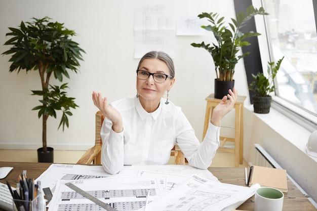 Porträt einer erfahrenen älteren architektin mittleren alters in stilvollen gläsern und weißer bluse, die an ihrem arbeitsplatz mit zeichnungen des architekturprojekts auf schreibtisch sitzt und sich über gut gemachte arbeit freut
