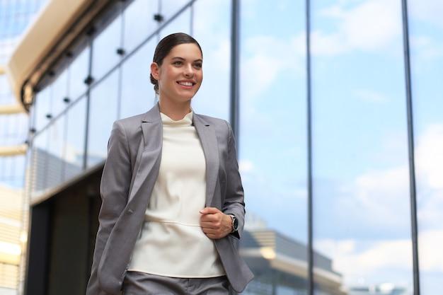 Porträt einer erfolgreichen geschäftsfrau im anzug, die beim gehen im freien wegschaut.