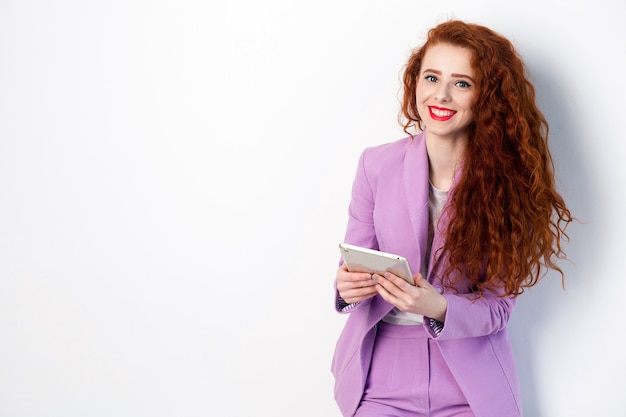 Porträt einer erfolgreichen glücklichen schönen geschäftsfrau mit rot-braunem haar und make-up im rosa anzug, der tablette hält, kamera mit einem zahnigen lächeln betrachtend. studioaufnahme auf grauem hintergrund.