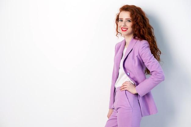 Porträt einer erfolgreichen glücklichen schönen geschäftsfrau mit rotbraunem haar und make-up im rosa anzug. blick in die kamera mit einem zahnigen lächeln, studioaufnahme auf grauem hintergrund.