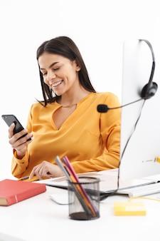 Porträt einer erfolgreichen kundenbetreuerin mit mikrofon-headset, die smartphone während der arbeit im callcenter hält