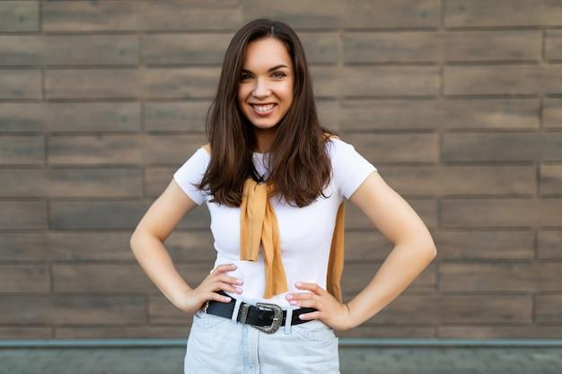 Porträt einer erfolgreichen lächelnden, fröhlichen, glücklichen jungen brunet-frau, die lässiges weißes t-shirt und jeans mit gelbem pullover trägt, der in der nähe der braunen wand auf der straße steht und spaß hat.