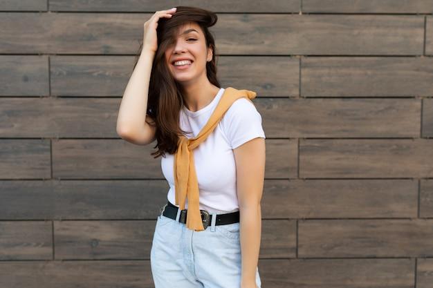 Porträt einer erfolgreichen lächelnden fröhlichen glücklichen jungen brunetfrau, die beiläufiges weißes t-shirt und jeans trägt