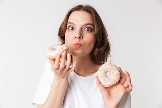 Porträt einer erfreuten jungen frau, die einen donut isst