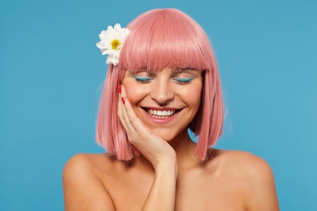 Porträt einer erfreuten jungen pinkhaarigen frau mit bob-haarschnitt und roter maniküre, die erhabene handfläche auf ihrem gesicht hält, während positiv mit geschlossenen augen lächelnd, isoliert
